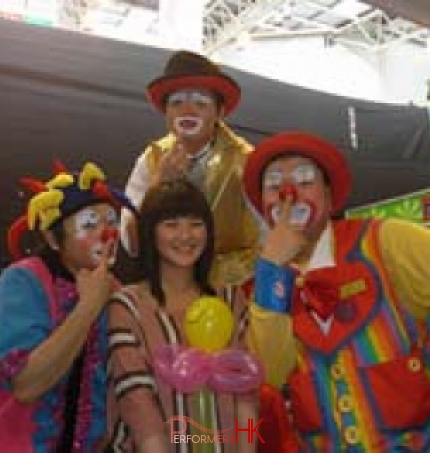 Tony and other clowns poses with a female guest holding her balloon