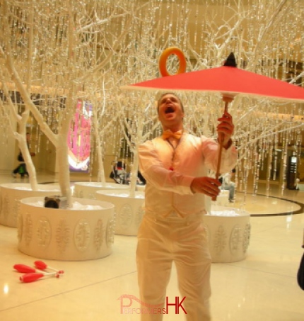 Juggler wearing white , juggling with umbrella and ring at a Hong Kong Christmas corporate event