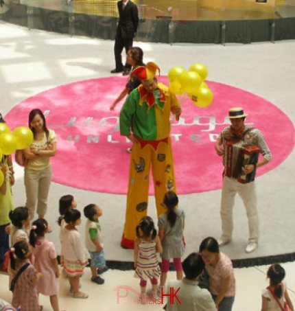 The stile walker wearing a patch jester stilts costume ,giving balloons away to children at shopping mall event.