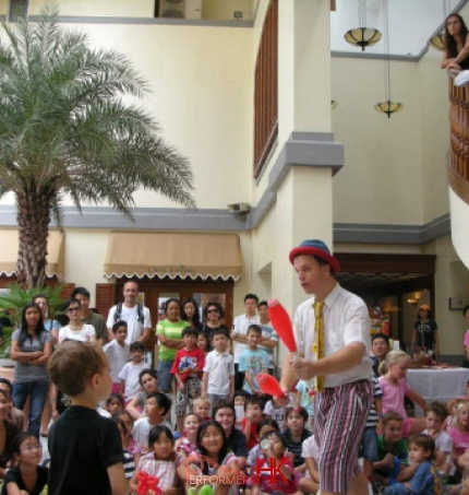 Performer doing a juggling trick in front of kids audiance