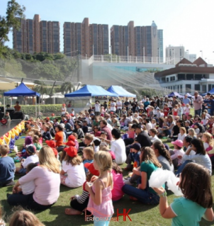 Magician Juggler at the Hong Kong cricket club doing a stage with a huge family crowd seated in front