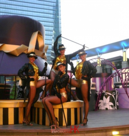 4 dancers in front of giant hat prop at a mall in Hong Kong