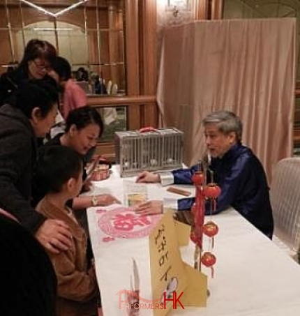 The Hong Kong bird fortune telling master explaining the card to five ladies at a corporate event