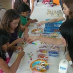 Two staff is assisting the children to decorate their own crafts at a corporate event