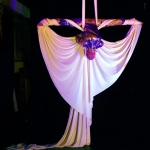 Performers show their skills by manipulating silk clothes in midair.