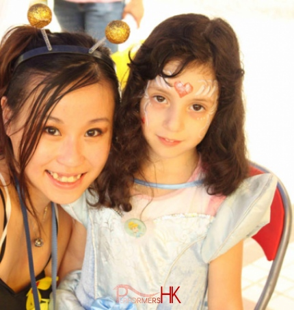 Face painter posing with child wearing princess makeup