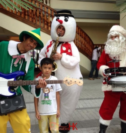 Three strolling magicians playing at Repulse Bay dressed as an elf, snowman and santa