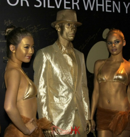 4 female Models standing with gold human statue performer all standing in front of a back drop