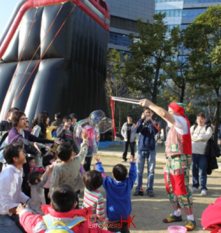 The children is trying to catch the bubbles at a Hong Kong corporate Christmas event