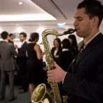 Sax player delivering soulful music at a dinner event.