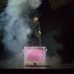 Wing performing illusion magic on stage.