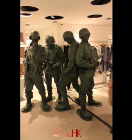 Four human living statue toy soldiers standing in a clothing shop