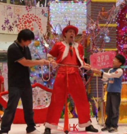 A Hong Kong funny clown performing the rope through the body trick with two volunteer helper from the audience , the try to pull the rope with tight on the entertainers body at a Xmas shopping mall function