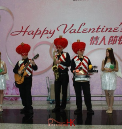 Roving three piece band with drum sax and guitar walking around Hong Kong airport wearing valentine day costumes