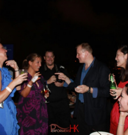 Hong Kong roving magician performing card magic trick to the lady in purple dress who holding a card at a corporate cocktails event