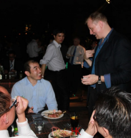 Walk around Magician in HK performing table card magic to four gentlemen at a roof top corporate event in Wan Chai
