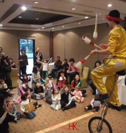 Hong Kong Unicyclist performing three cups juggling on the unicycle at a Family day event