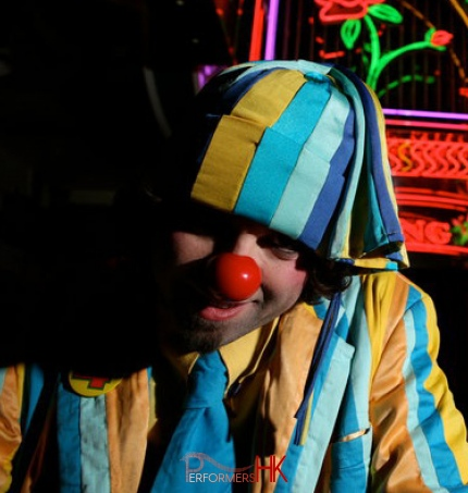 Alfie wears colourful clothes and red nose for his performances
