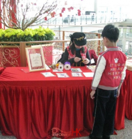 A female artist working on a Chinese knotting gift for child on a red table with the background of a flower pot at the Hong Kong Airport