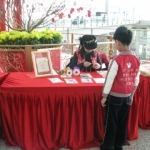 Chinese New Year event at Hong Kong Airport. Artist making Chinese knotting for child.