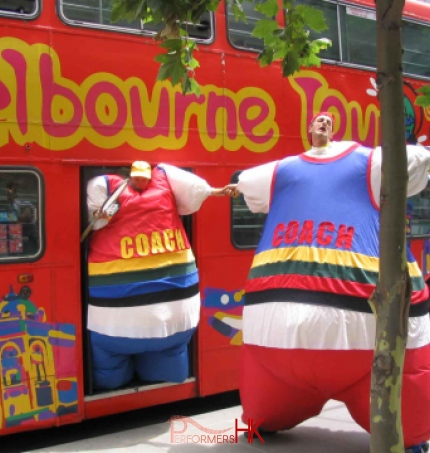Hong Kong stilt-walker in a blue inflatable coach costume pulling other stilt-walker in a red inflatable coach costume from a bus