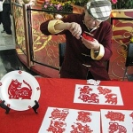Zodiac paper cutting artist cutting Chinese zodiac animal from a red paper at Hong Kong airport