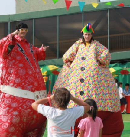 Two inflatable stilts walkers dressed as Elvis and Hawaiian costume roving for a family day in Hong Kong