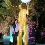 Golden stilt walker holding huge chupa chup and posing for picture with a lady