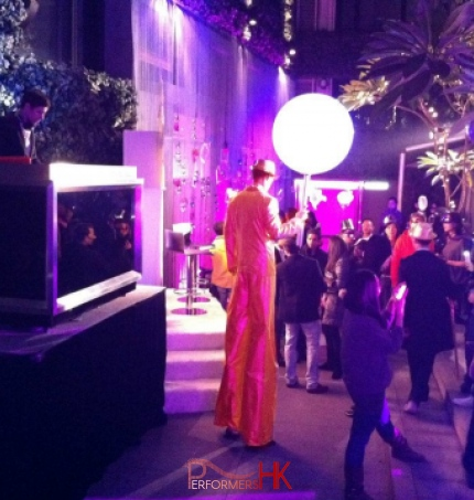 Stilt walker wearing golden costume and holding a giant chupa chup