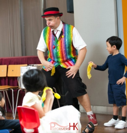 A Clown in Hong Kong invited a little boy audience to perform with him, they shake the yellow silks together and ready to turn it to a different color at a school event