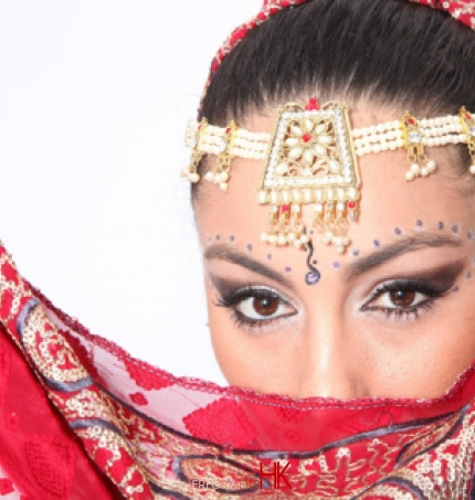 A head shot of a Bollywood Dancer in Hong Kong wearing Red traditional Bollywood dance costumes for a cocktails event
