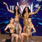 Four Hong Kong  Bollywood Dancer wearing gold and black costumes posing for a corporate event.