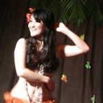 Gorgeous hula dancer smiling cheerfully on stage while dancing gracefully.