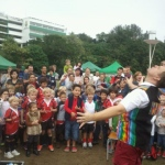 Performer balancing a glass of water on three chopstick whilst a large crowd watches