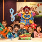 Tony the clown poses with kids at a party.