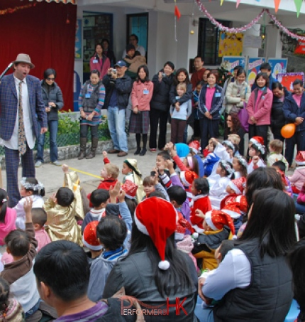 The juggler asking for a volunteer and a lot of the audience putting their hands at a Hong Kong Christmas event