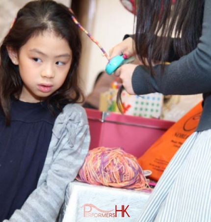 A lady wrapping the girl hair to braid with a little string machine at a corporate children event