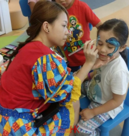 Face painter in HK very focused, drawing a dolphin face paint on a child at a school event