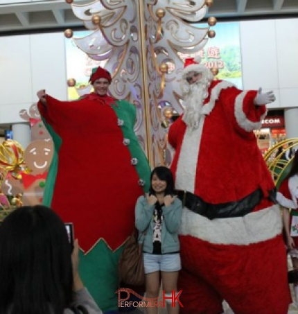 Two giant inflatable stilt walkers walking around an airport terminal in Hong Kong with a gingerbread mascot