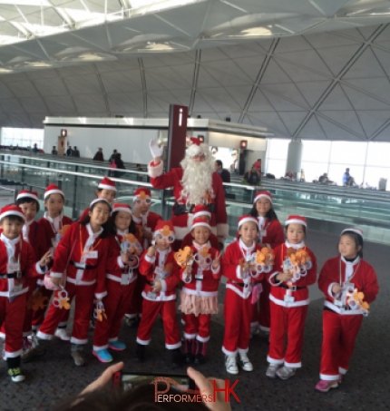 santa clause at hong kong airport with children in red santa costumes
