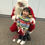 Santa with small child at the airport