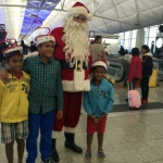 Santa with kids at the airport next to the travellators