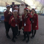 Tall Santa Rowan with Cathay flight staff at the airport boarding gates