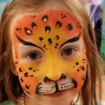 Leopard face paint with sparkle stickers.