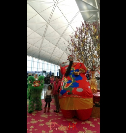 HK stilt-walker in giant inflatable Choi Sun costume at airport Chinese New Year event