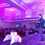 HK magician standing on a purple stage performing his stage act with the mobile borrow from the audience at a corporate annual dinner