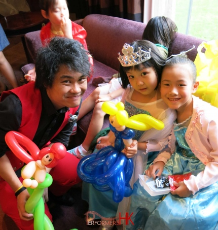 Roving Balloon artist in HK twisted two princess balloons for two children dressed in a Elsa costume at a kids birthday party