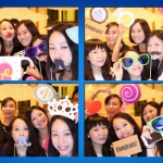 ladies wearing funny props taking pictures at photobooth stall
