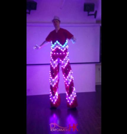 Stiltwalker in a LED costume posting at a studio in Hong Kong