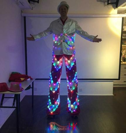 Stiltwalker in a LED costume with sliver jacket taking picture in Hong Kong